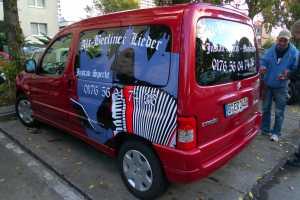 Heckscheiben- und Seiten-Beklebung am Musikanten-Fahrzeug mit Klebefolien und Digitaldruck